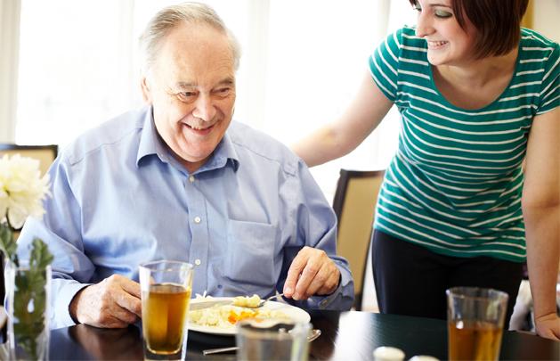 Carer taking care of elderly man